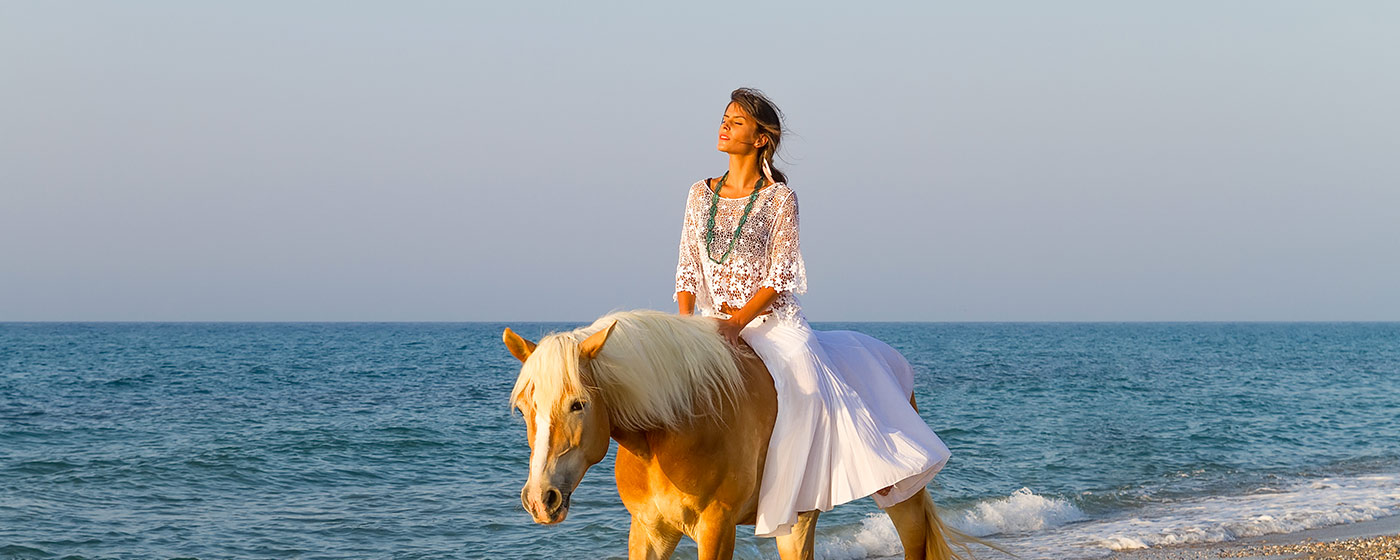 a women enjoys the sun on a horse at the beach