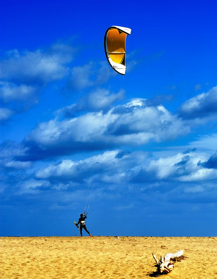 Tourist practice paragliding during his holidays in Sardinia